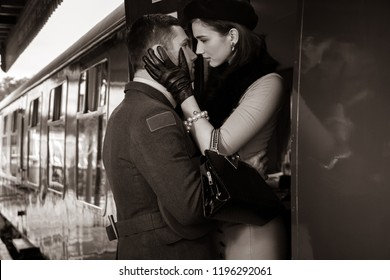 Vintage couple, handsome man in uniform, kissing goodbye his lover on railway station platform as train is about to leave.