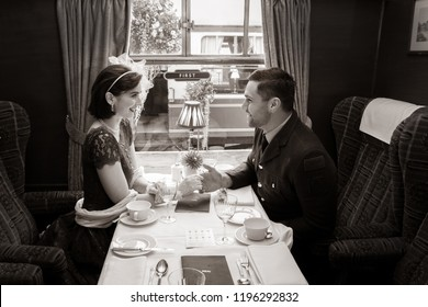 Vintage couple, handsome man in uniform, beautiful woman in dress, holding hands over dining table of train carriage