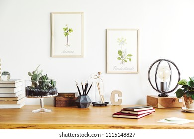 Vintage, creative home office interior with wooden desk, books, notebooks, romantic illustrations of plants, table lamp and office accessories. Stylish space for freelancer.