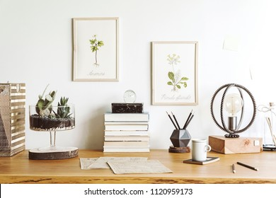 Vintage, creative home office interior with wooden desk, books, laptop, romantic illustrations of plants, table lamp and office accessories.