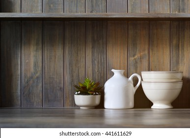 Vintage crockery and small plant on a dark wooden background. De-focused
