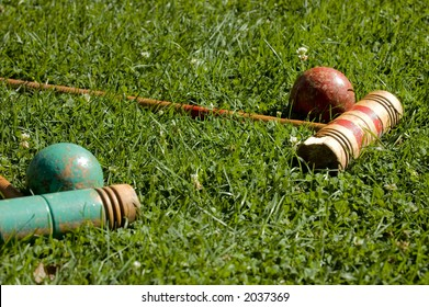 Vintage croquet mallets and balls on the lawn.