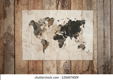 Vintage Crumpled paper texture on wooden table with Dark spots as Shape of World Map