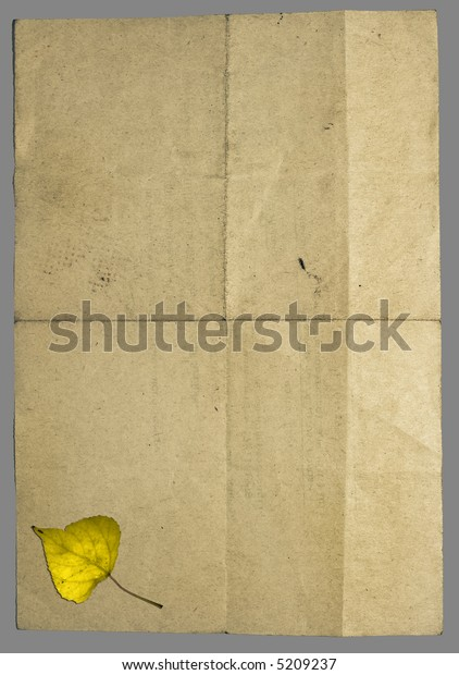 Vintage crumpled retro style paper with many folds and with yellow fallen autumn leaf in lower part. Image isolated on grey with clipping paths