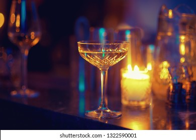 Vintage crystal glass on a blurred background. The atmosphere of a romantic dinner by candlelight.