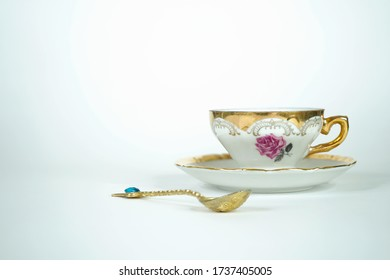 Vintage cup with golden spoon, elements from the Victorian era with handmade decoration.