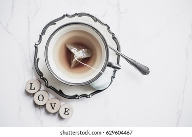 Vintage cup of tea and love word, top view
