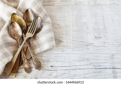 Vintage cutlery and checkered napkin on wooden table, copy space.