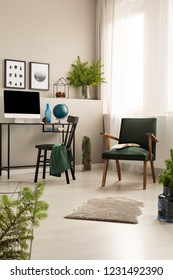Vintage dark green armchair in trendy home office with black wooden chair and desk with all in one computer