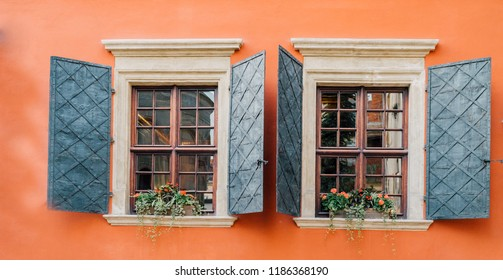 Vintage decorated windows with blinders shutters on worn orange wall. Historical city elements Classic European architecture Postcard concept Travel inspiration Luxury estate background.