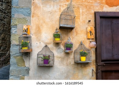 Vintage decoration on a stone wall with flowers in empty bird cage in the old provincial Tuscany town Cortona, Italy.