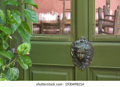 Vintage decorative bronze escutcheon in the form of a female head in the Baroque style on a green glazed door. In the foreground is a blurred branch with leaves. Abandoned house in an old park.