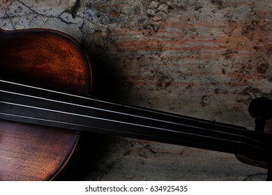 Vintage deep brown violin on a rough colorful textured background