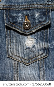 Vintage denim texture background: jacket close-up. Blue torn pocket. Stylish torn denim background. Closeup pocket on blue denim jean and button. Fashionable jacket, fashion background.