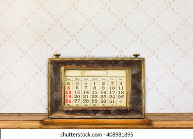 Vintage desktop calendar on a wooden table in front of retro wallpaper