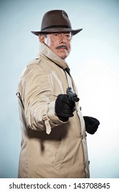 Vintage detective with mustache and hat. Holding gun. Studio shot.
