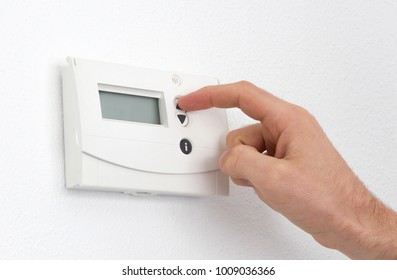 Vintage digital thermostat hanging on a white wall - Man adjusting