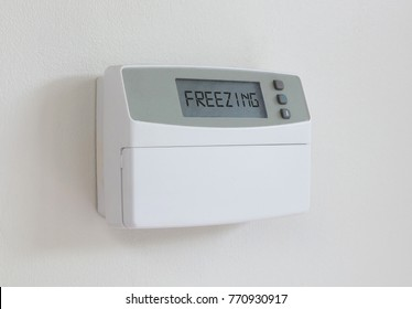 Vintage digital thermostat hanging on a white wall - Covert in dust - Freezing