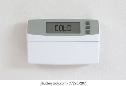 Vintage digital thermostat hanging on a white wall - Covert in dust - Cold