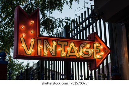 Vintage direction arrow sign lit up with light bulbs