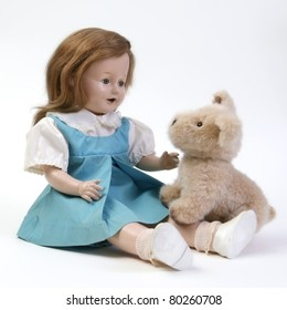 Vintage doll in blue & white dress with stuffed puppy seated on white background