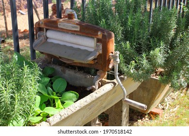 Vintage domestic clothes wringer with rollers and crank handle mounted onto concrete trough