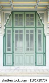 vintage door. A exterior details of traditional Thai vintage door in green color.