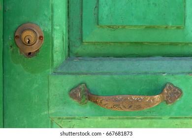 Vintage door handle with door lock on wood painted door in green color