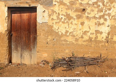 Vintage door on Adobe Facade. Wooden front door of a home. Front view of a weathered Oaxaca adobe brick house with a small pile of sticks for burning as fuel set in earth in front. Horizontal shot.