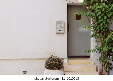 Vintage door with postal box on white wall