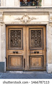 Vintage double door entrance of old building in Paris France. Aged wood doorway and ornamental stucco fretwork wall of ancient stone house in classical architecture. Antique front door. Travel Europe.