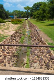 a vintage drainage ditch constructed of rocks and concrete