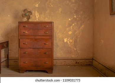 Vintage dresser in an old worn room with peeling paint