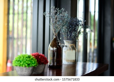 Vintage dried flowers in glass bottle, set on the table in a dining room.
