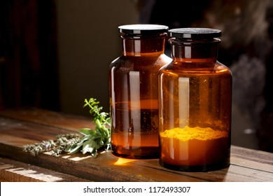 Vintage dusty medical or chemical bottles on a wooden table