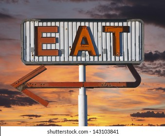 Vintage eat arrow sign in with sunset sky.