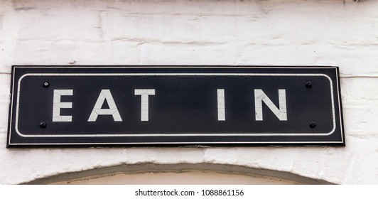 Vintage eat out sign in white painted brick wall of restaurant in Stratford-upon-Avon in Warwickshire, England.