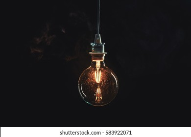Vintage edison lightbulb on dark background with bright yellow shining wire