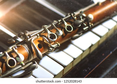 Vintage effect photograph. Antique clarinet leaning on piano keyboard.