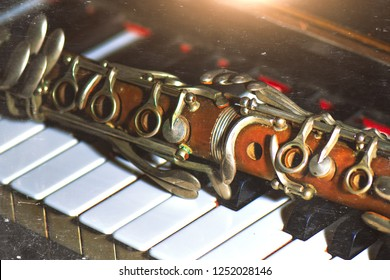 Vintage effect photograph. Antique clarinet leaning on piano keys.