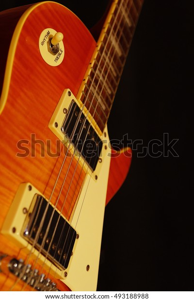 Vintage electric guitar closeup on the black background. Shallow depth of field.