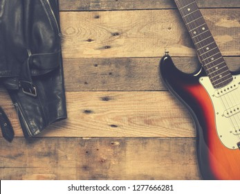 Vintage electric guitar with a leather jacket on a rustic wooden plank, vintage flat tone stylized