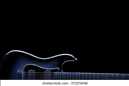 vintage electric guitar shape on black , blue image