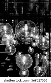 Vintage electric light lamp bulbs hanging on the ceiling in the dark room with copy space as background - Black and White