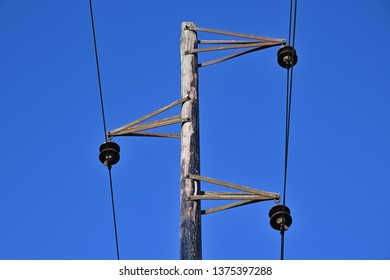 Vintage electric pole and wires. An old overhead power line and single wood utility pole structure. Electrical power transmission and distribution cables.