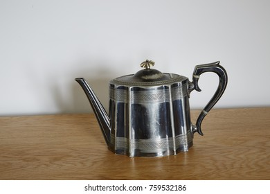 A Vintage Electroplated teapot standing on a cuboard
