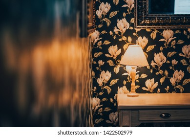 Vintage elegant room interior with cozy light. Table, lamp, mirrow and beautiful wall pattern.