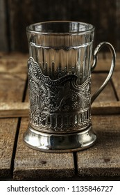 Vintage empty glass for tea with cup holder on rustic background. Old kitchen utensils, selective focus