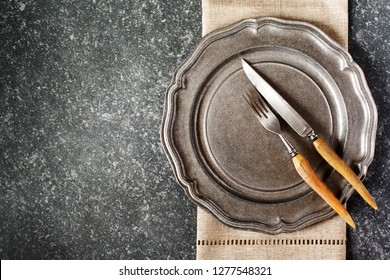 Vintage empty plate and fork and knife with napkin on dark grey stone background, copy space, top view