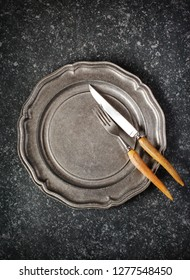 Vintage empty plate and fork and knife on dark grey stone background, copy space, top view